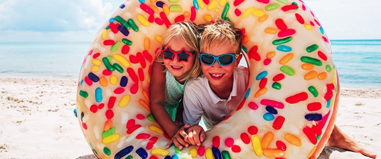 young boy and girl on beach sitting inside a doughnut shaped inflatable ring