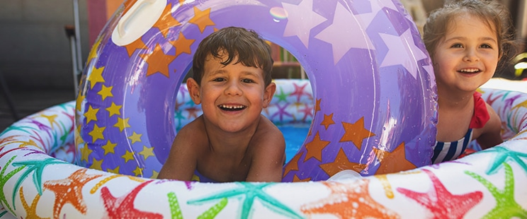 young boy and girl in inflatable wader pool with purple inflatable floatie