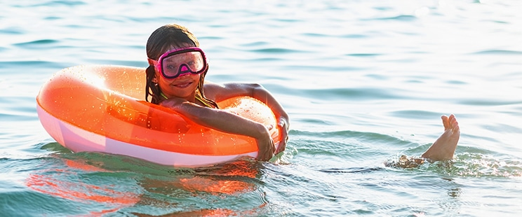 girl floating on water in inflatable orange ring
